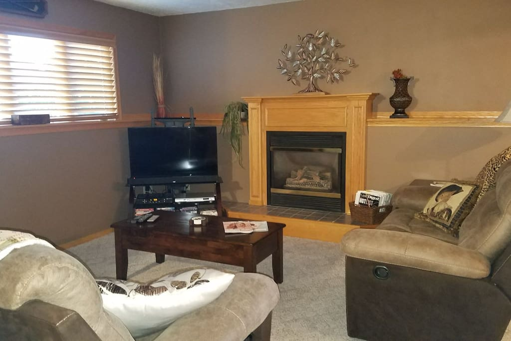 Cozy lower level living room with plenty of seating! great spot on hot summer days or chilly winter evenings with the fireplace at the touch of a thermostat!