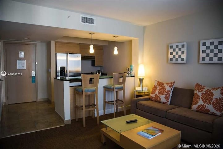 Living room with modern glass top high table, full kitchen with all amenities, cooking isle, granite countertop.  Sofa bed can be converted to double size sleeper for 2 people.