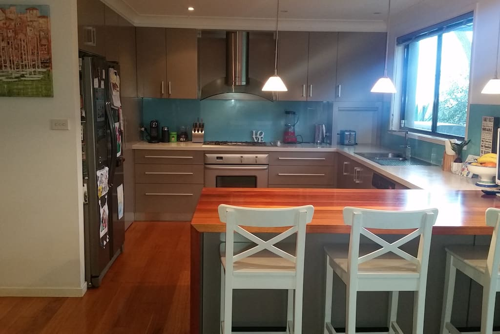 Open plan kitchen with gas stove, caesarstone benchtops and stainless steel appliances - perfect for entertaining