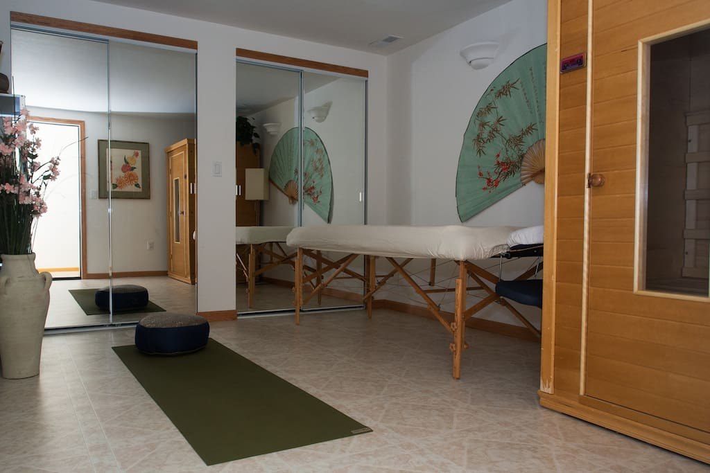 Spa room has professional massage table, sauna, and room for yoga.