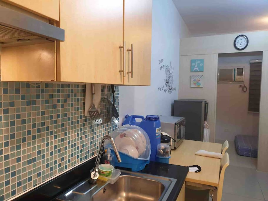 Kitchen area, electric stove w/ exhaust, microwave and refrigerator, rice cooker, pots and pans