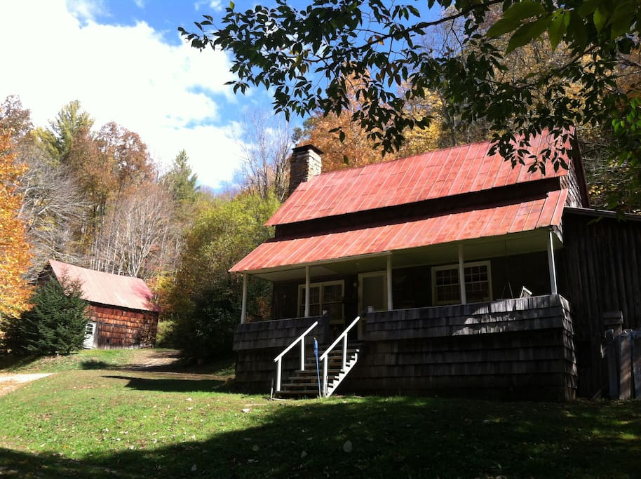 front of cabin with old barn in background + 16 acres