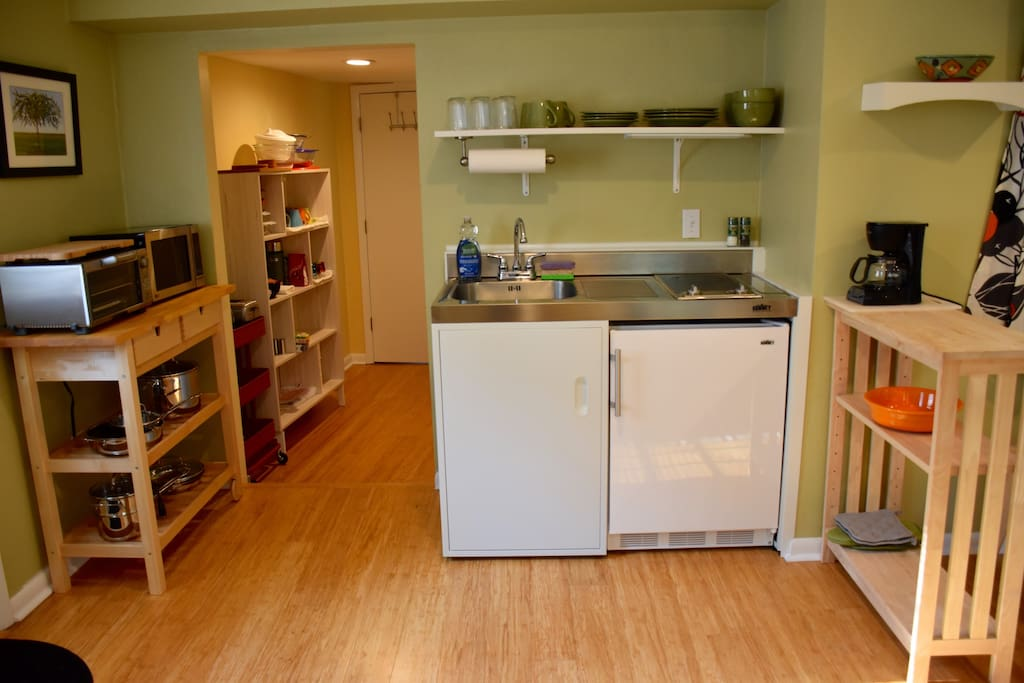 Fully equipped kitchenette with hallway leading to private bathroom.