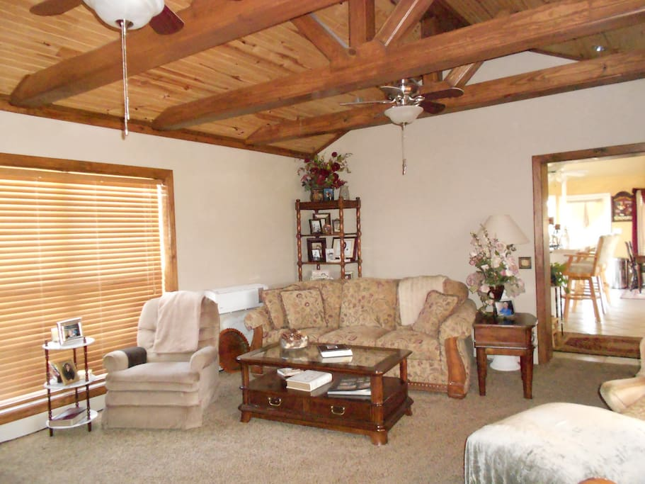 Living room, wood beam ceiling with two ceilings fans.