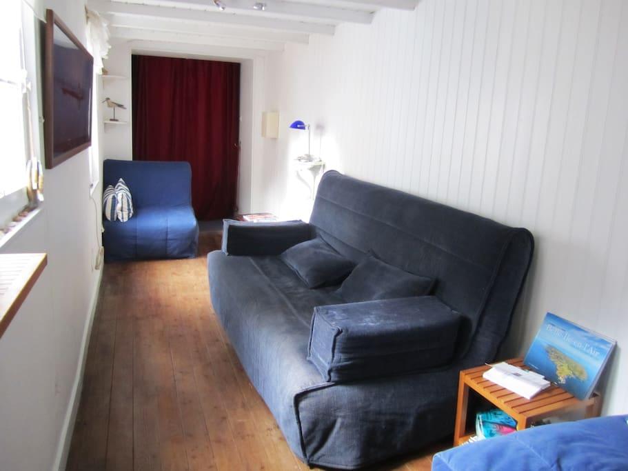 Le salon, l'entrée est derrière le rideau rouge.