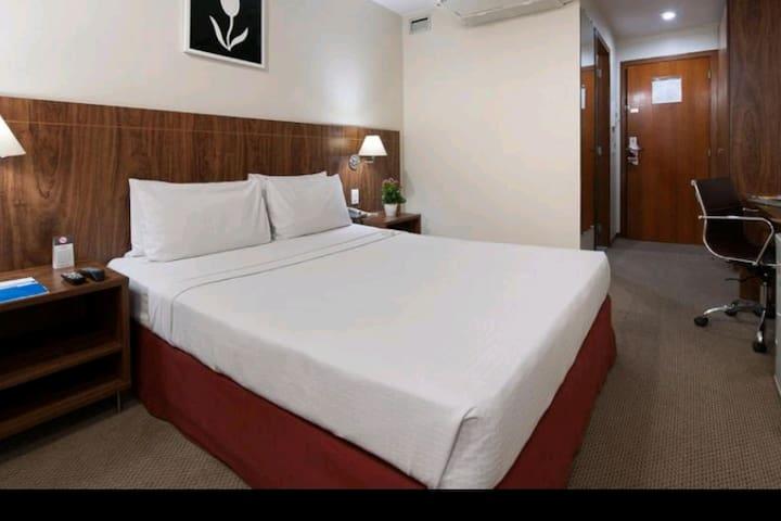 Quarto com cama de casal confortável, ar condicionado, televisão LCD, poltrona e mesa para trabalho.