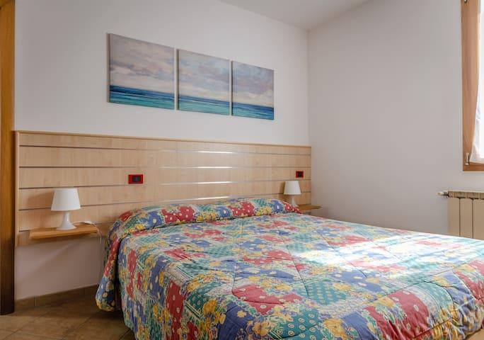 Camera da letto matrimoniale con ampio armadio e ventilatore a soffitto