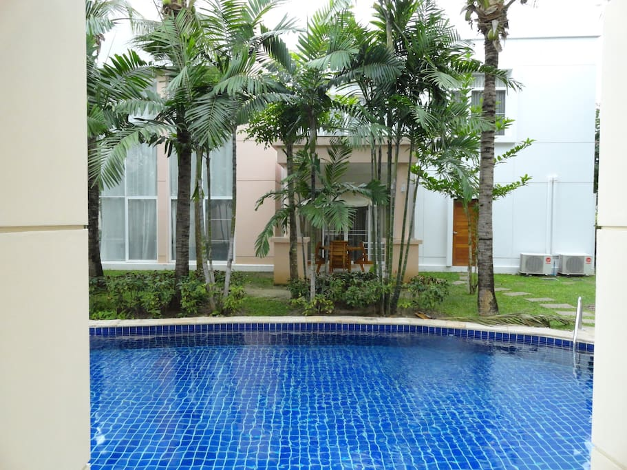 view of house opposite balcony with pool in between