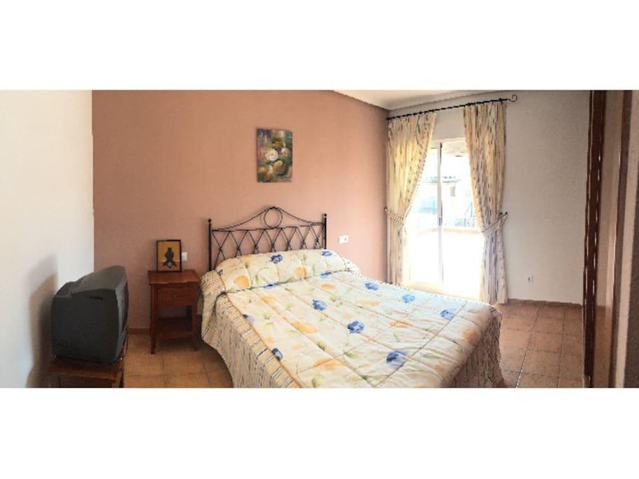 Dormitorio independiente con cama de matrimonio y armario empotrado, acceso a la terraza