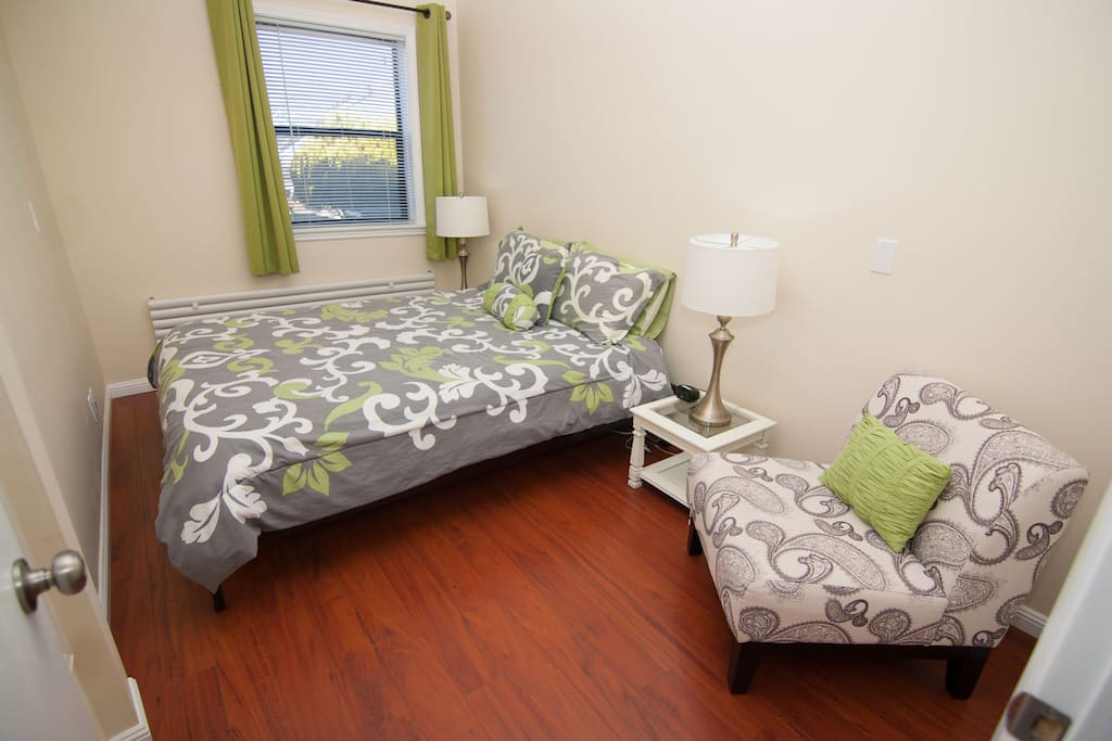 The master bedroom, facing the garden, and adjacent to the living-dining room. It features a good quality queen bed, a chair, and a large closet with shelves to store luggage, bags and more. In the closet you will also find a Pack 'n Play crib, an iron and small ironing board.
