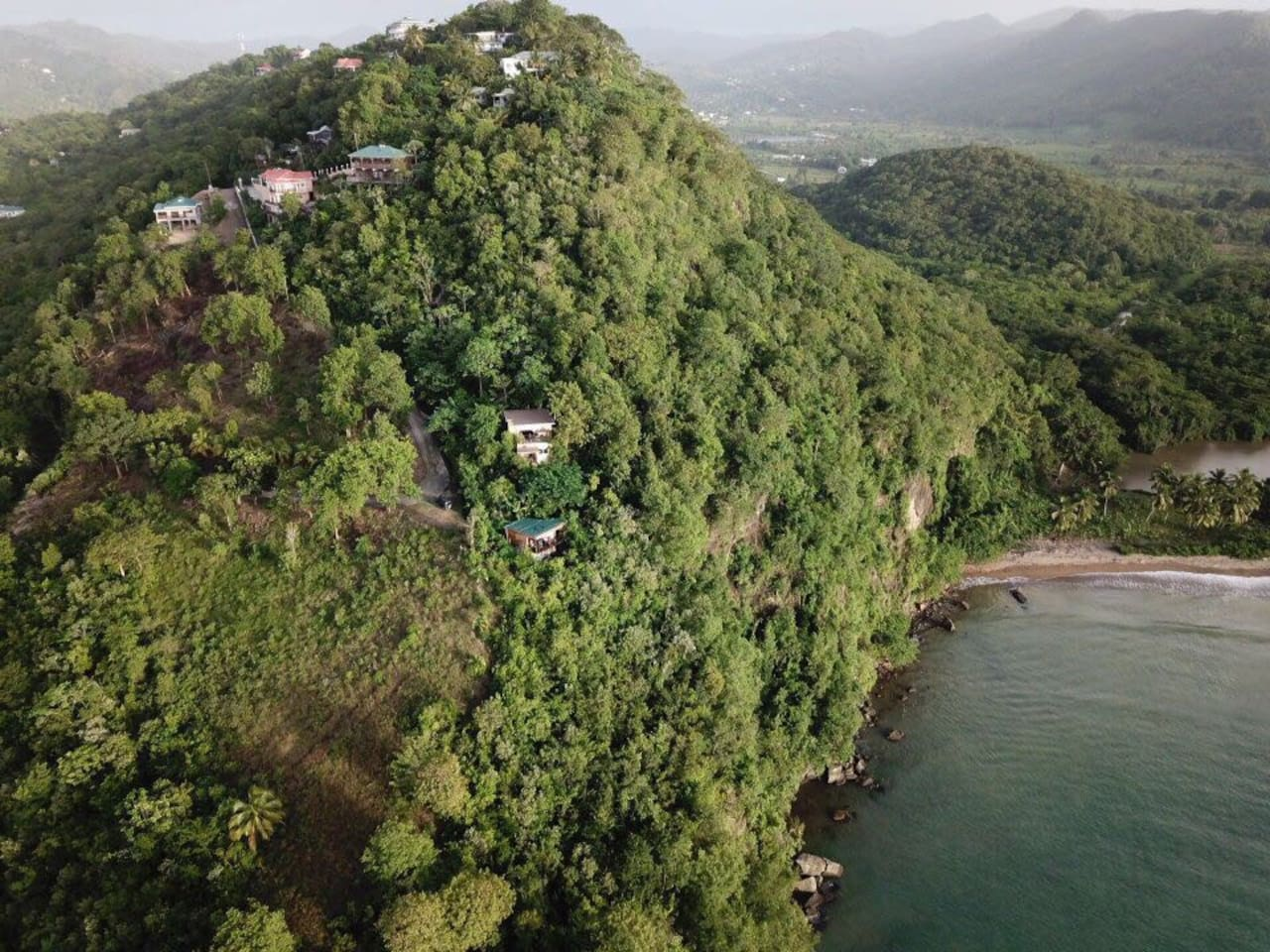 The Hummingbird Hangout with its green roof is in the centre of the photo below the Treehouse (yellow house) - wow what a view! Even local people are amazed when they see our view!
