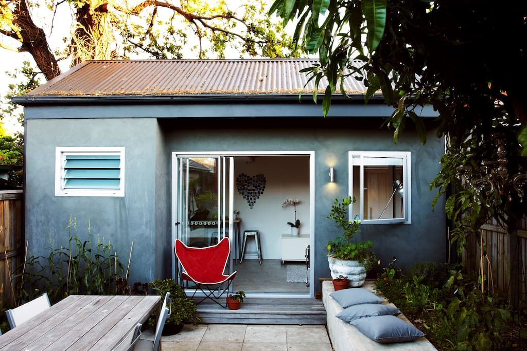 Exterior of The Garden Studio, with outdoor table where you can enjoy your meals.