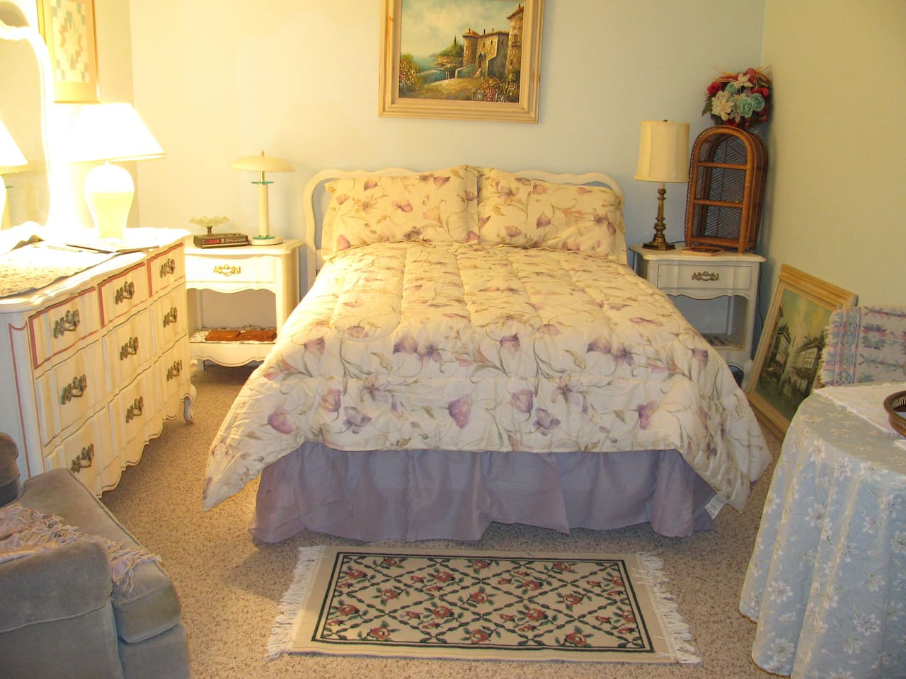 Bedroom with full size bed, triple dresser, 2 end tables. A chair, table, TV and 2 folding chairs