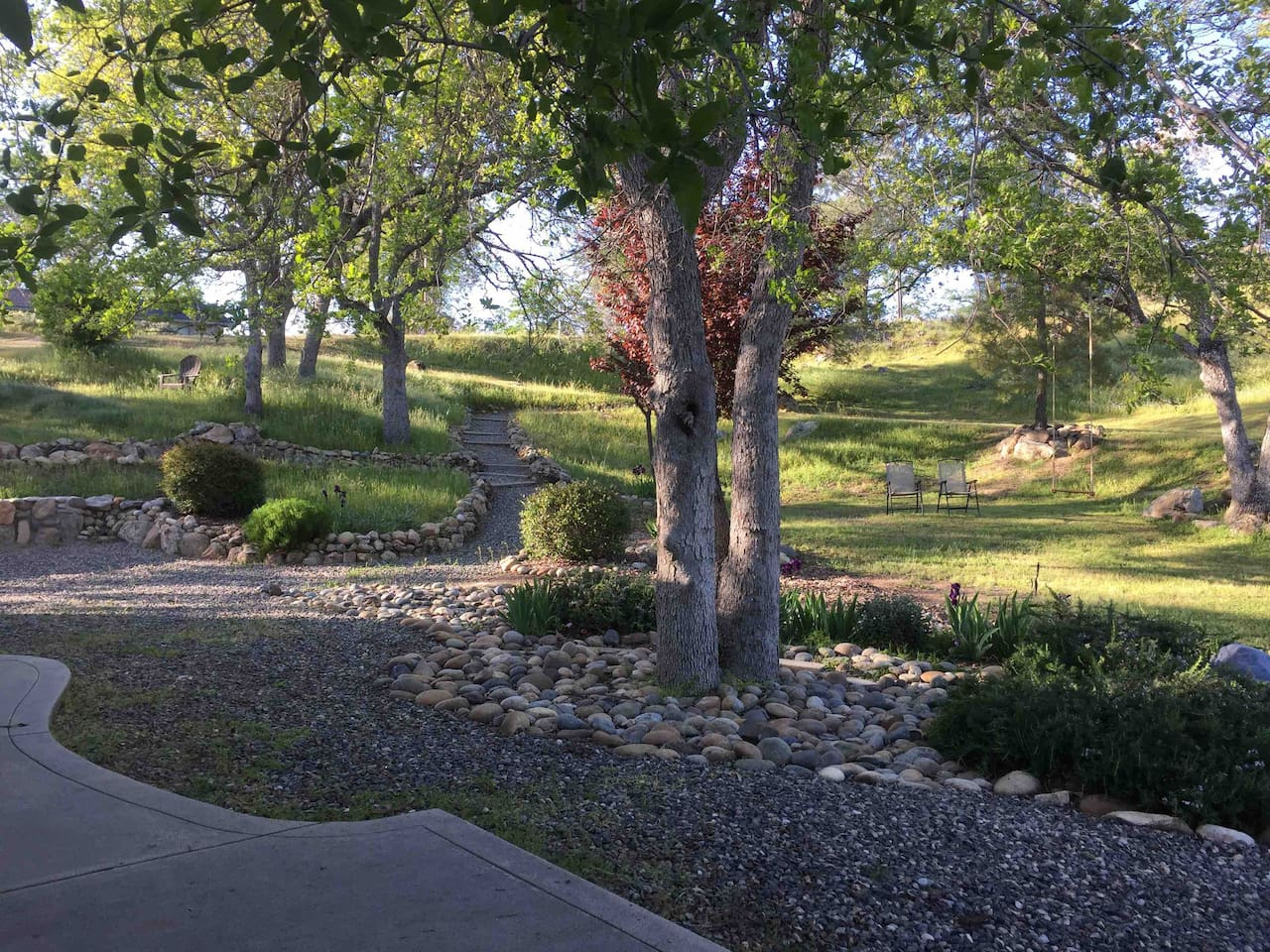Yard view in Spring with rock pathways and adult swing!