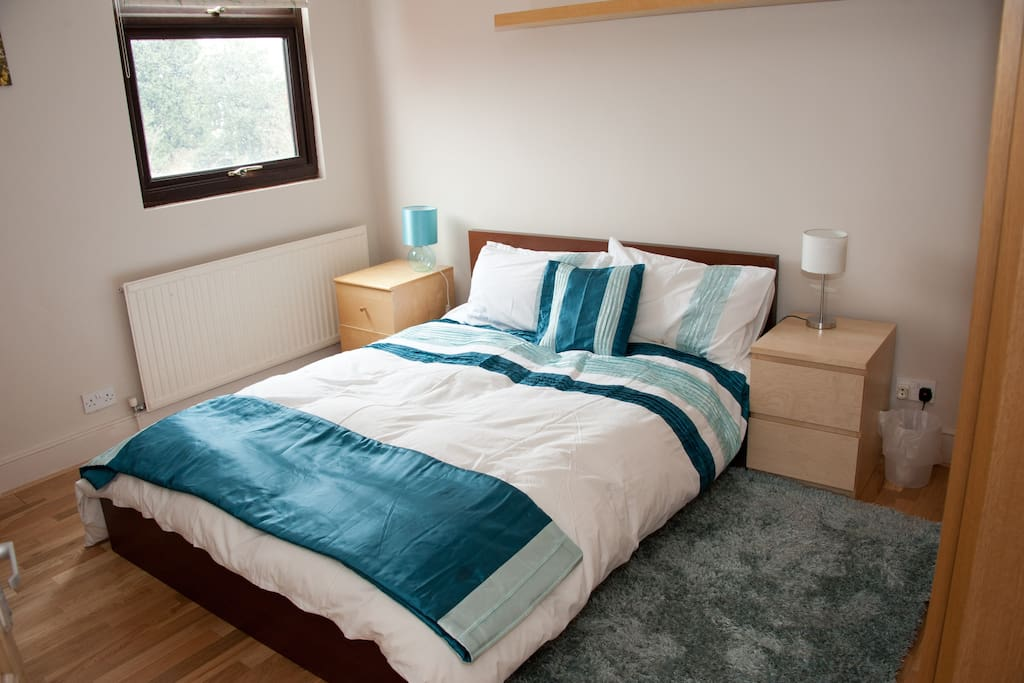 Second bedroom - double bed. Bright and airy overlooking garden and trees