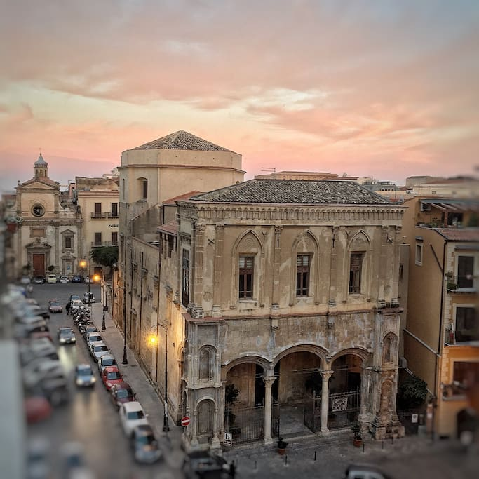 During the sunset time. The view from the balcony on the square where the building is. This is Santa Maria La Nova's church