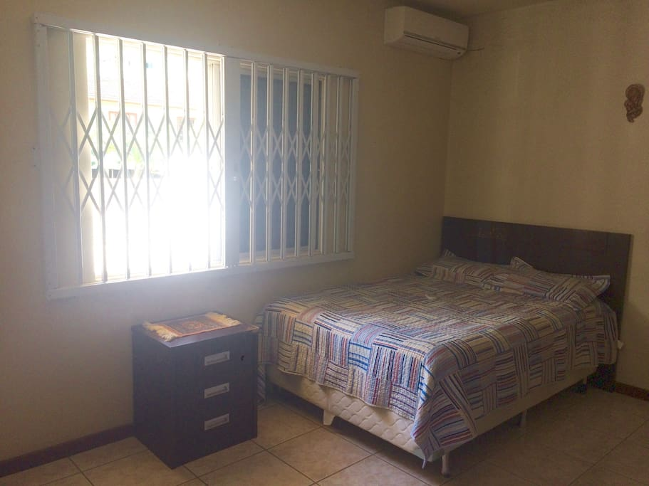 Suíte com cama de casal, ar condicionado, guarda roupa amplo, criados mudos com gavetas e balcão.