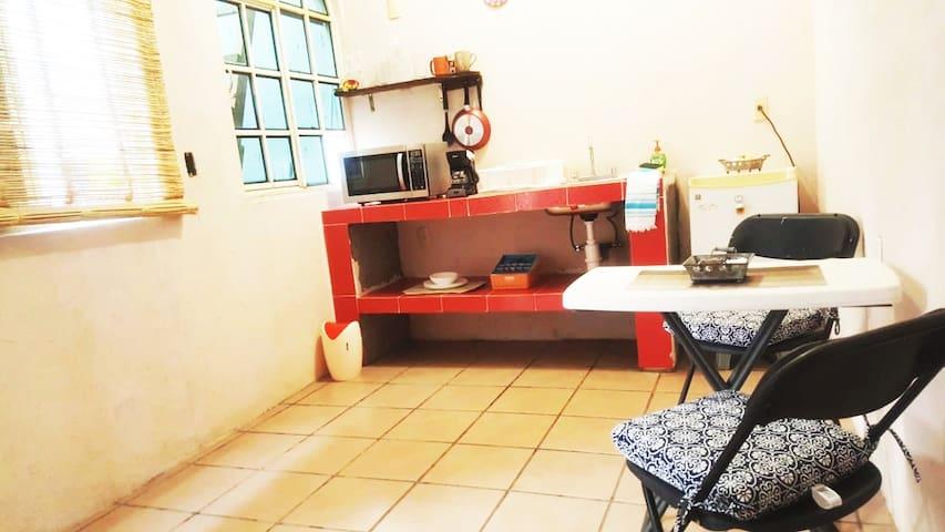 Estudio con una mesa, sillas donde podrás disfrutar de alimentos o trabajar.. cuenta con ventilador, frigobar, microondas, cafetera, tazas, 3 juegos de cubiertos, vasos,  1 sartén, 1 olla, 2 utencilios para cocinar.