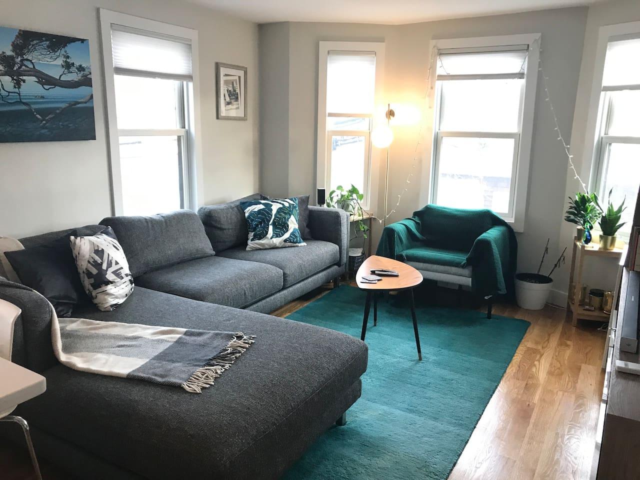 "Light filled living room, furnished with a plush designer sofa and 45"" smart TV"