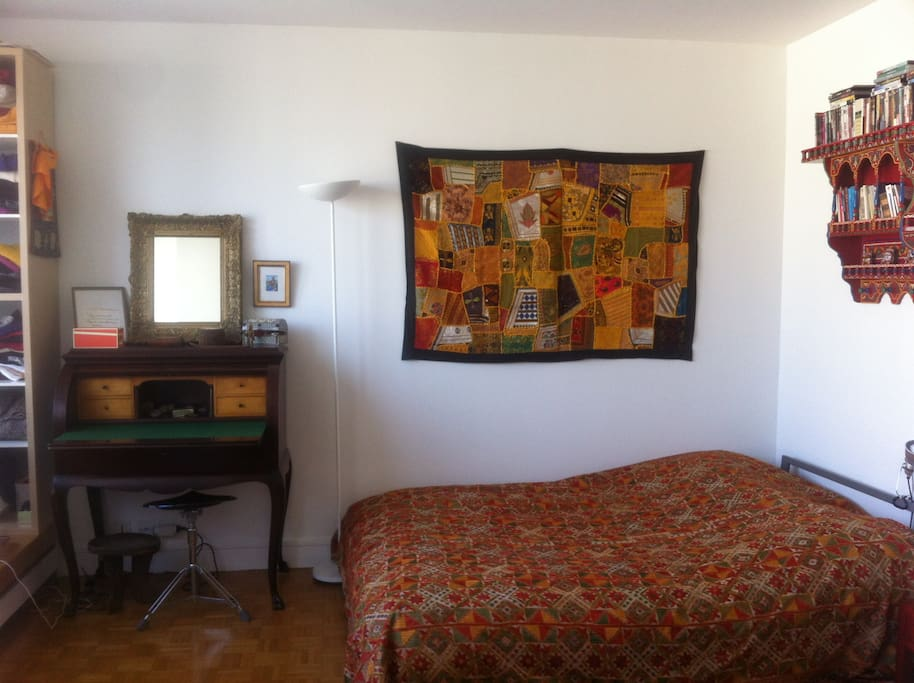 Bedroom with a double bed and antique desk to write postcards to the loved ones back home.