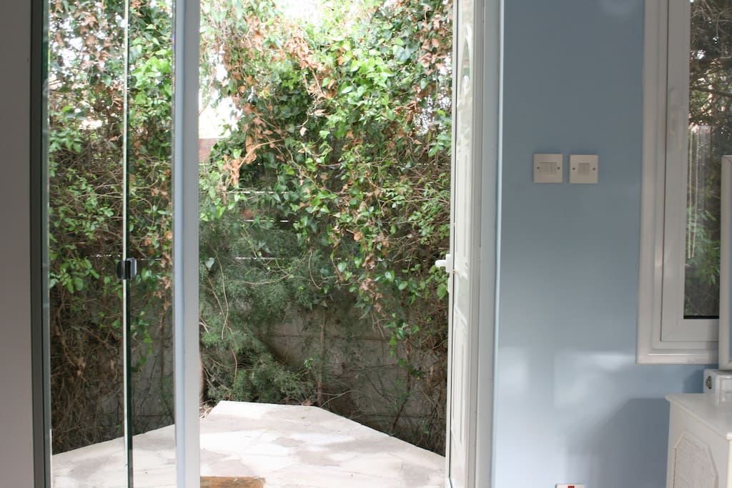 The door opens outwards. The surrounding area is covered in trees and foliage as well as ivy for extra privacy.