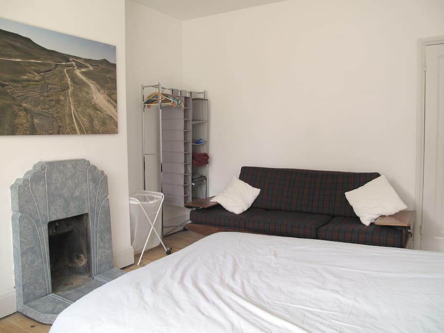 Upstairs bedroom - fireplace (not in use) laundry hamper, clothes rail with hanging shelves, sofa