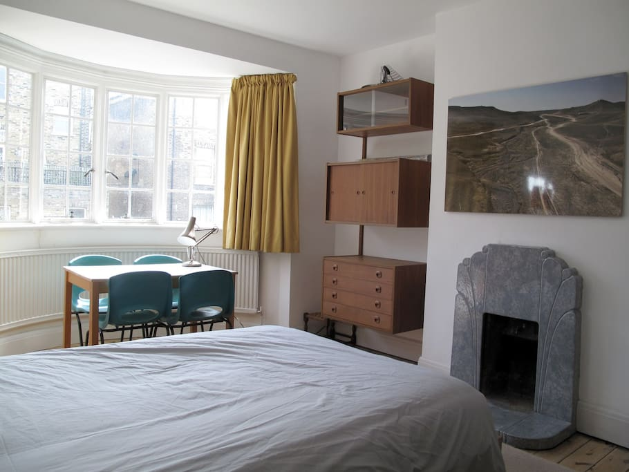 Upstairs bedroom - bay window overlooking rear gardens, table and chairs, cado unit, fireplace (not in use)