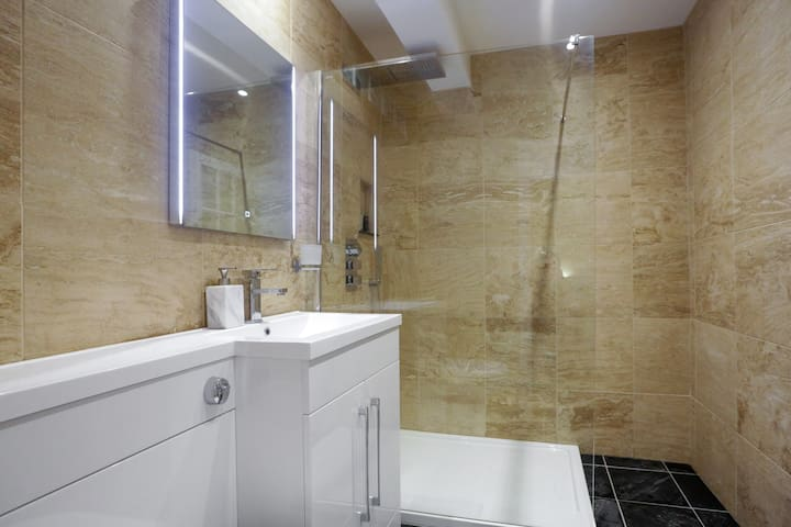 Luxury travertine tiled bathroom with 3 shower options. Rain,waterfall and hand held. LED lit mirror.