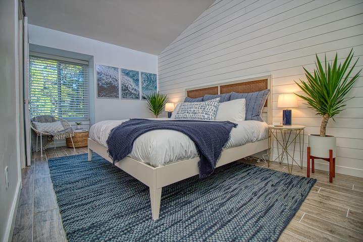Loft-style bedroom with contemporary, coastal vibes.