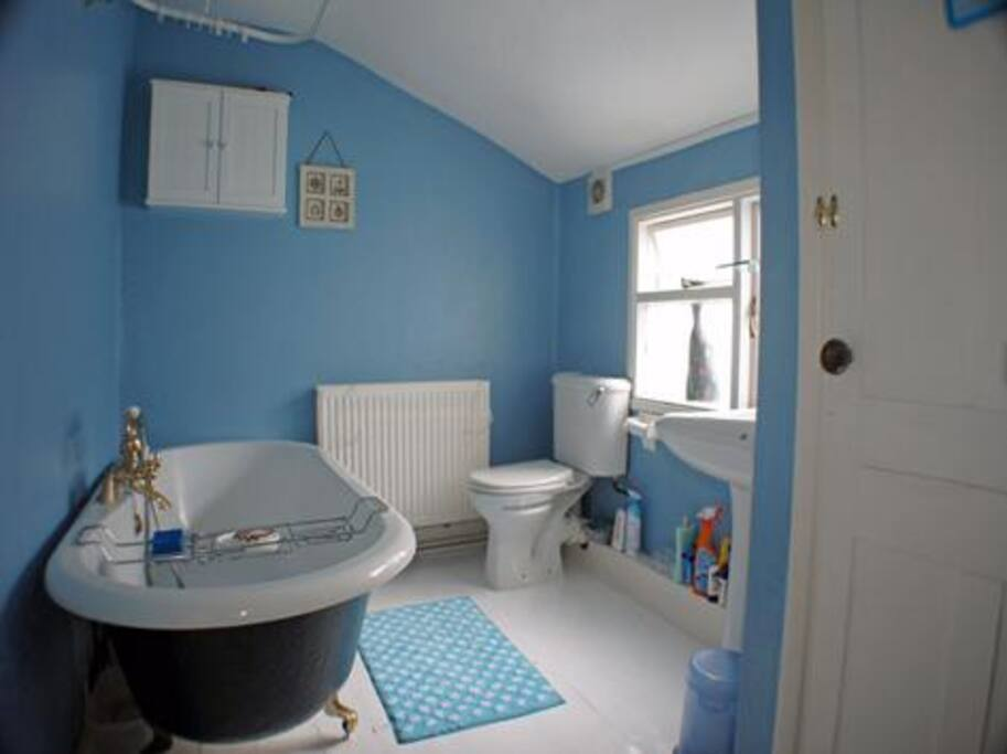 Bathroom with Victorian rolltop bath, handheld shower attachment, WC, sink and storage cupboards.