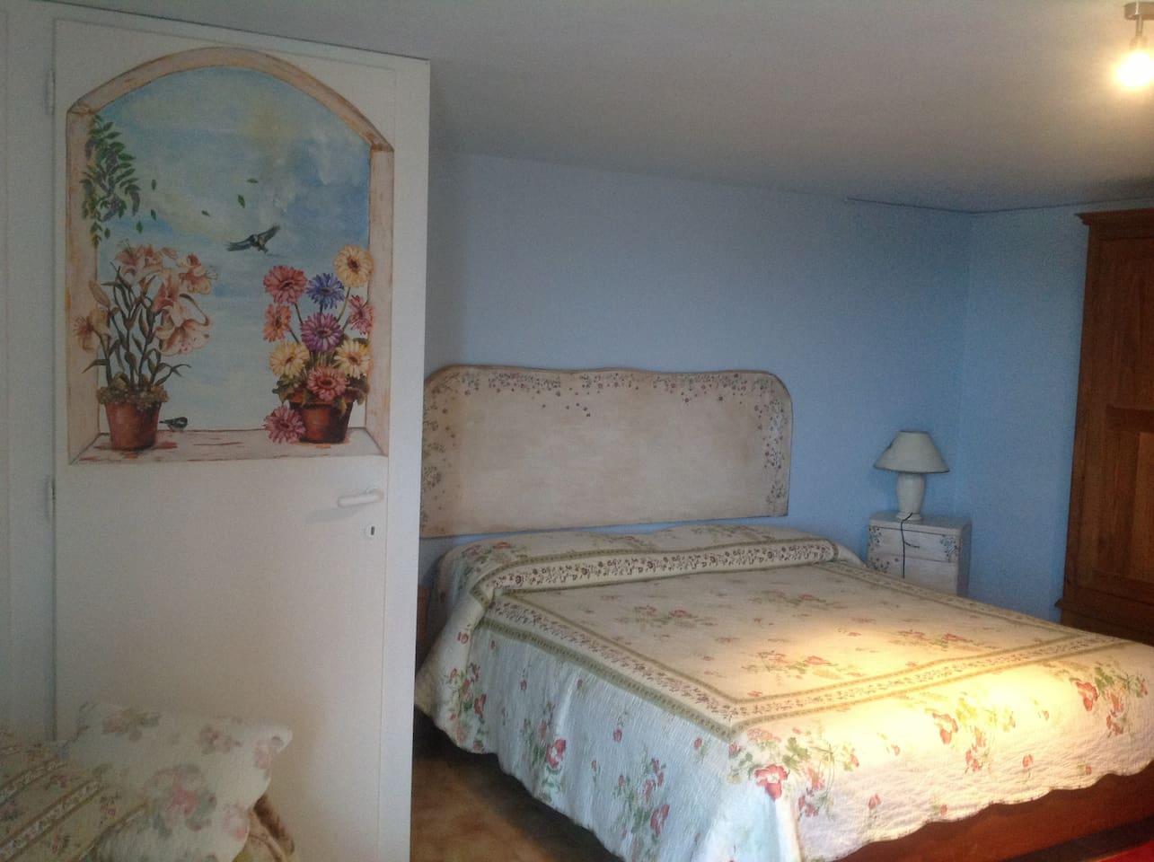 La camera è tripla con bagno all'interno ed è particolare perché piena di dipinti inoltre è unita ad una graziosa cucina con vista sul giardino.