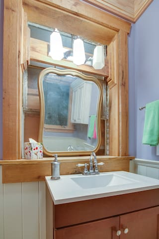 The downstairs bath has a vintage mirror and vintage lighting.