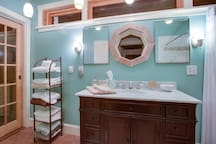 The master bath has a vanity with a marble top. That's chestnut around the octagonal window.