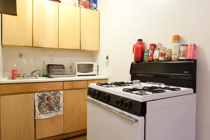 EFFICIENT KITCHEN WITH COFFEE MAKER, MICROWAVE, BLENDER, TOASTER OVEN, RICE MAKER AND BASIC FOOD ITEMS FOR COOKING, TONS OF FRESH GROCERIES IN THE AREA