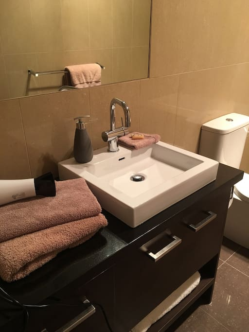 Clean modern bathroom with hair dryer & shower over bath.