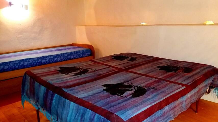 camera con divano letto a due posti e un letto 1 piazza e mezzo