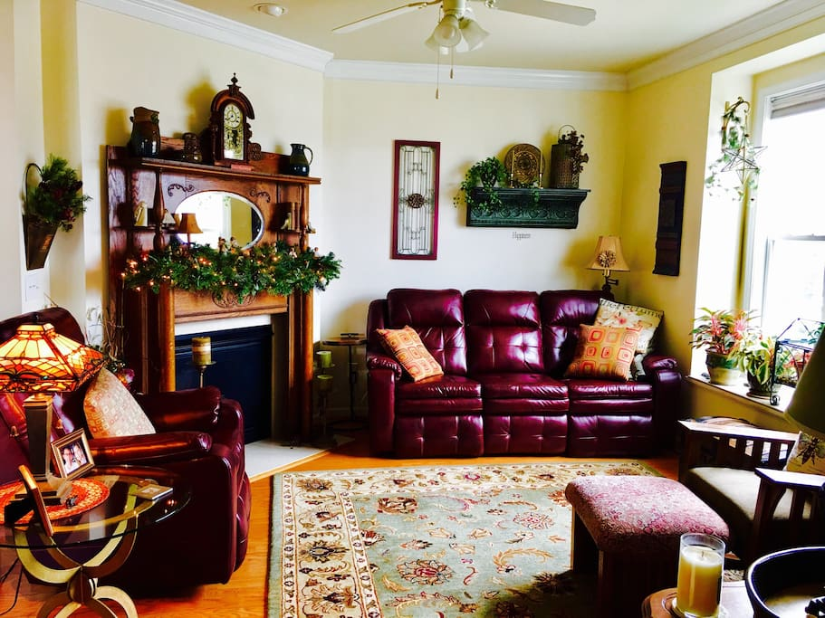 Reclining couch and chair, cozy fireplace with historic mantle and cable TV.