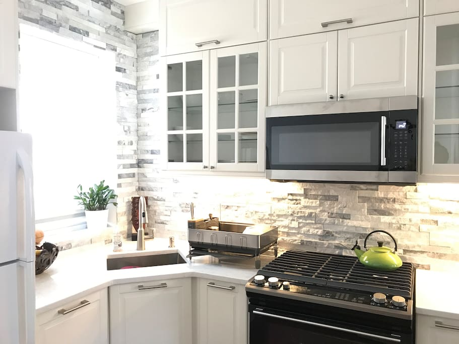 Newly-renovated kitchen with brand new stove, oven, microwave, and dishwasher.