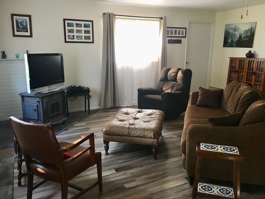 Living room has large sofa, chair, recliner chair, LCD TV, blue ray player and movie collection. Living room also has black out curtain.