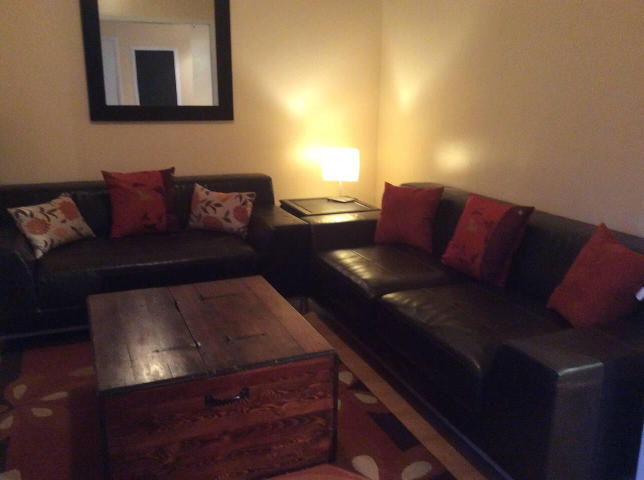 Salon accueillant ouvert sur la salle à manger et la cuisine.