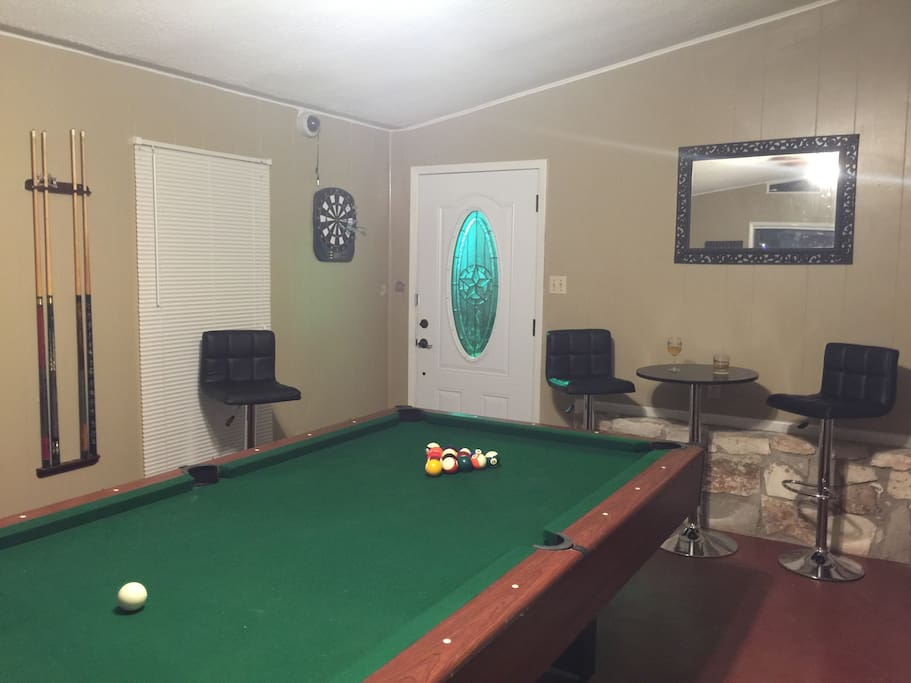 Pool table and dart board in game room
