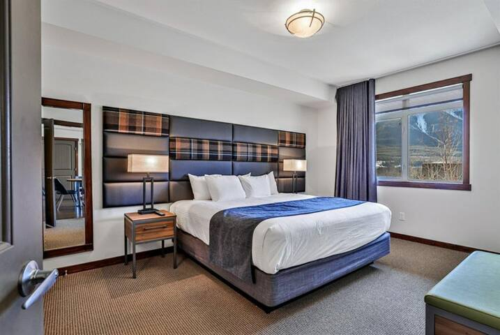 Deluxe bedroom #1 with a king bed and a breathtaking mountain view from the window