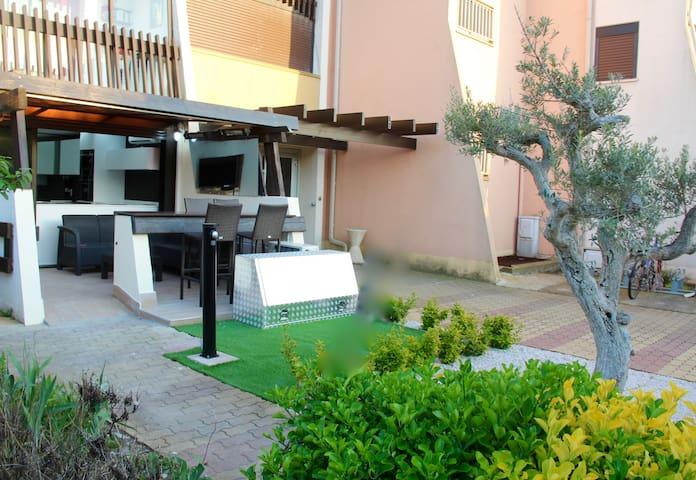 Jardin privatif  avec douche extérieure pour le  rinçage lors des  retours ensablés  de plage ..