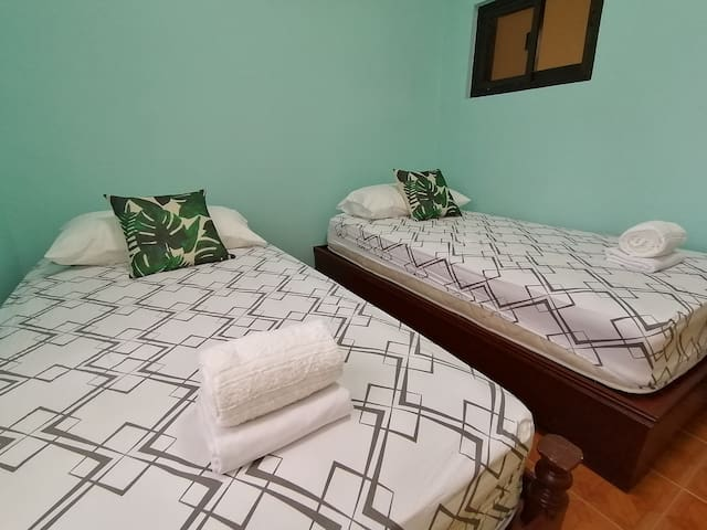 Room A of the extension house. Has 2 single beds, a cabinet, and an electric fan. Can accommodate 2 persons.