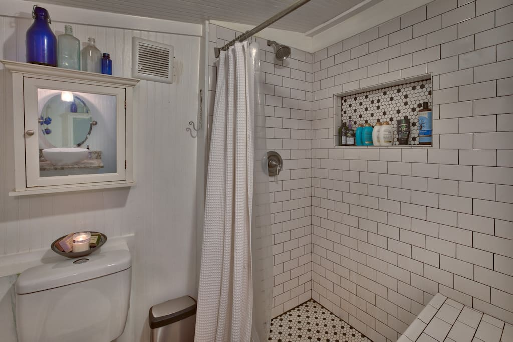 Full bath with walk-in tiled shower with bench seating
