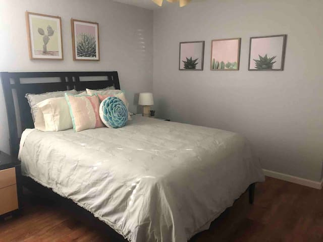 """Large master bedroom with spacious walk-in closet, queen bed and 50"""" smart TV."""
