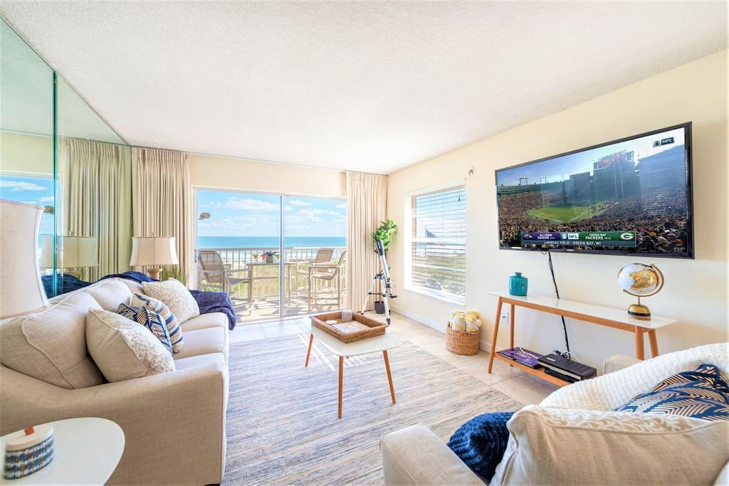 """Gorgeous beach casual living room with views from the ocean. Large 65"""" TV to catch movies & shows!"""