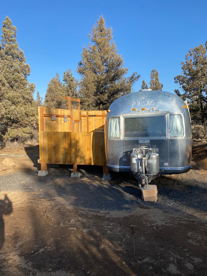 an old airstream with a fence