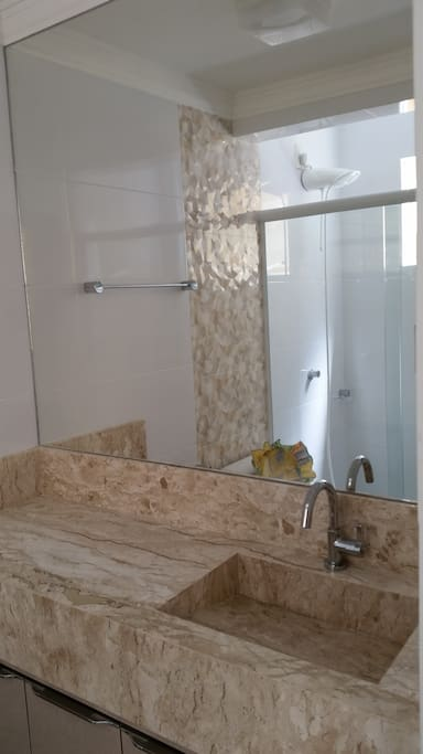 banheiro social em mármore e espelho grande.
