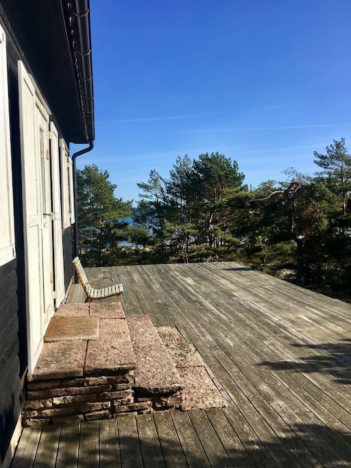 Stugan i renoveringsbehov med trädäck runt huset och utsikt över havet har långt till närmsta granne.